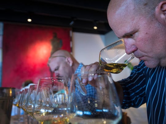 Regan Jasper, with Fox Restaurant Concepts, takes in the aroma of one of the white wines at The Arizona Republic Wine Competition at Tarbell's in Phoenix, on Monday, October 27, 2014. Twenty judges each graded 30 wines in the preliminary round, with around 140 Arizona wines competing for top honors.