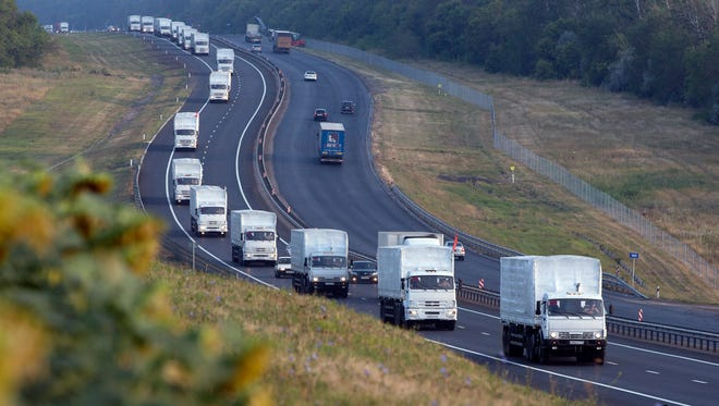 A convoy of white trucks allegedly filled with humanitarian aid moves from Voronezh towards Rostov-on-Don, Russia, early Thursday.