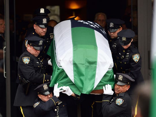 New York Police Department officers carry the casket