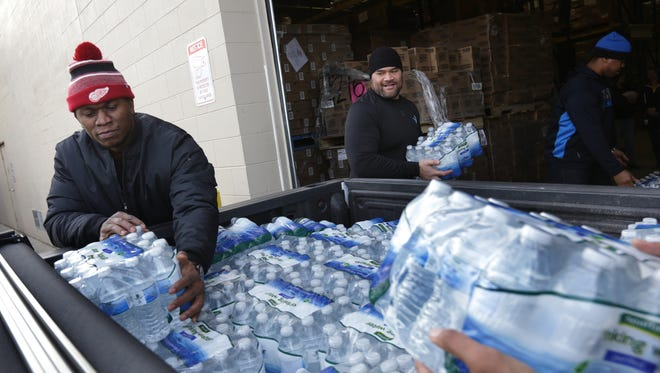 Detroit Lions defensive tackle Ziggy Ansah, left, and Haloti Ngata distribute some of the 94,000 bottles of water Ansah donated to Flint residents at a food pantry in Flint on Friday, January 22, 2016.