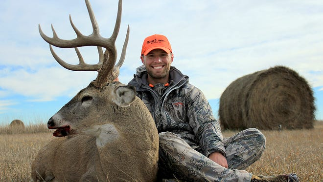 Jordan Miller, 28 of Sioux Falls, poses with a buck he shot.