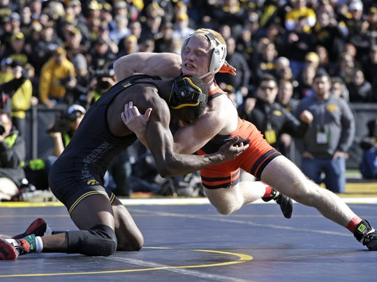 Oklahoma State's Chance Marsteller, right, wrestles with Iowa's Edwin Cooper Jr. on Saturday in the 157-pound bout in Iowa City, Iowa. Marsteller, a Kennard-Dale graduate, earned a 14-11 decision in his collegiate debut. Iowa won 18-16.