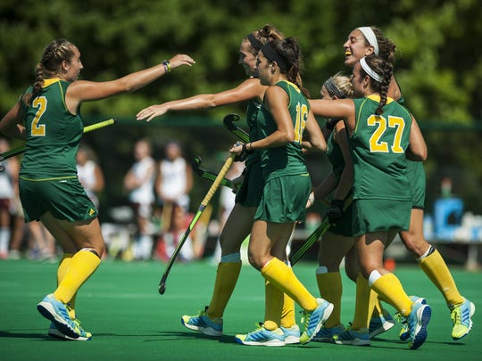 The UVM women's field hockey team celebrates a goal during an early season game at Moulton Winder Field.