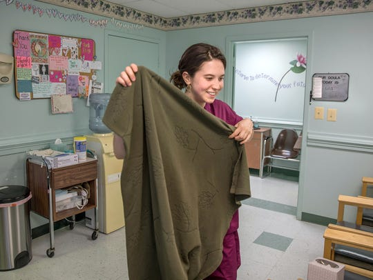 Lila, an abortion doula, gets a blanket for a patient