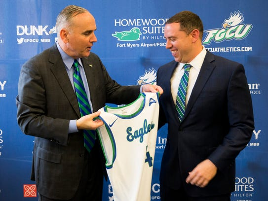 Florida Gulf Coast University athletic director Ken Kavanagh, left, presents longtime assistant coach Michael Fly with a jersey after Fly is officially promoted to lead the team as its new head coach during a public press conference at Alico Arena's Hospitality Suite on Thursday in Fort Myers.