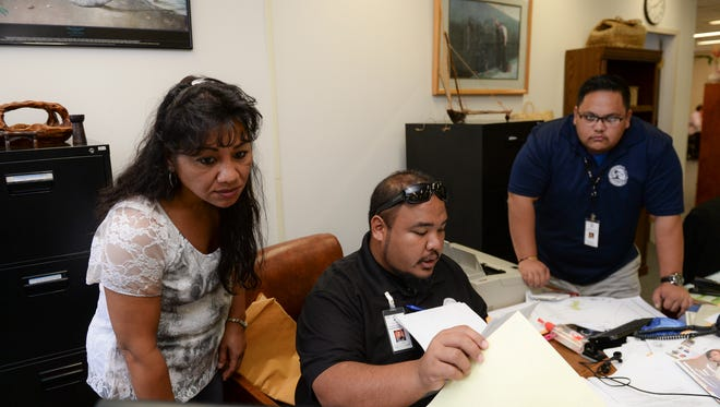 Guam Election Commission Program Coordinator Paciano F.N. Gumataotao, center, accepts affadavit of registration forms from volunteer voter registrar Grace Babauta, left, at the Guam Election Commission office.