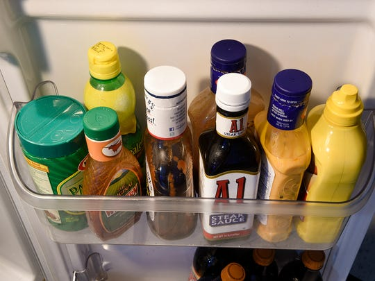 Bottles of expired salad dressing and other items sit in a refrigerator Thursday, Feb. 9.