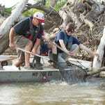 Fishermen pull a catfish out of water with limp line fishing method on Deepwater Creek near Clinton.