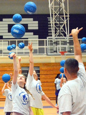 The Cavegirls basketball camp works on shooting form on Wednesday.
