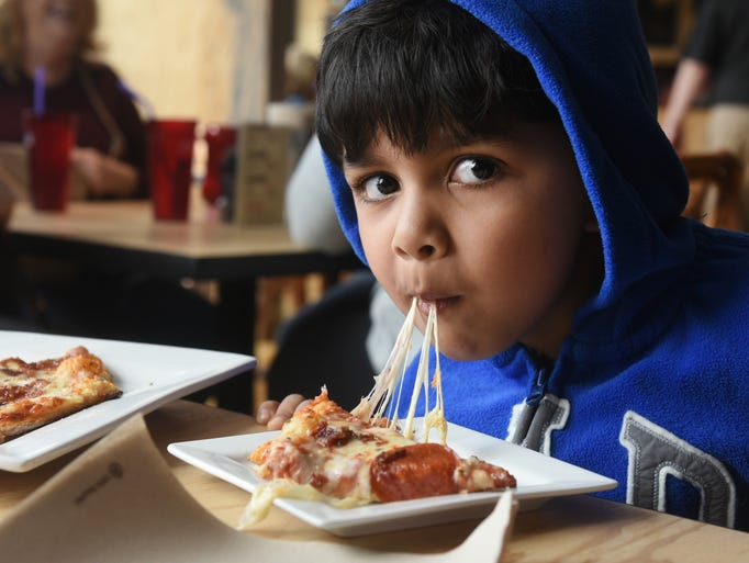 Ayan Dey of Birmingham eats a cheesy pepperoni pizza