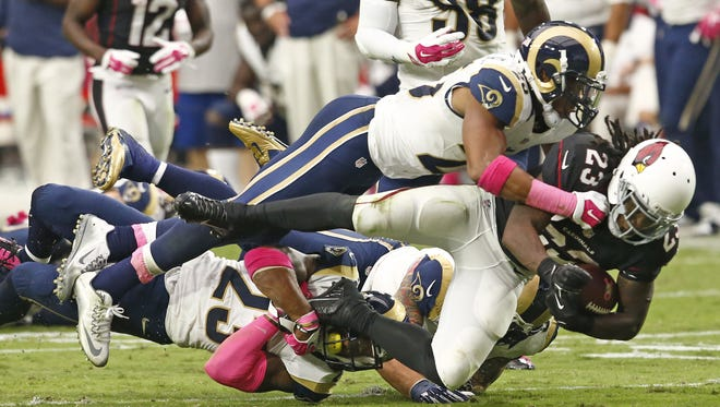 St. Louis Rams free safety Rodney McLeod (23) and St. Louis Rams strong safety T.J. McDonald (25) tackle Arizona Cardinals running back Chris Johnson (23) in the second half on October 4, 2015 in Glendale, AZ.