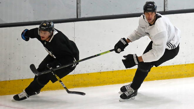 Bruins' Zdeno Chara, right, and Connor Clifton follow the action from along the boards during Tuesday's practice at Warrior Arena.