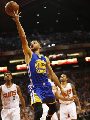 Golden State Warriors guard Stephen Curry (30) lays in the ball against the Phoenix Suns during the fourth quarter at Talking Stick Resort Arena in Phoenix, Ariz. April 5, 2017.