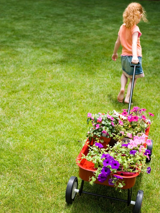 Girl pulling wagon with flowers