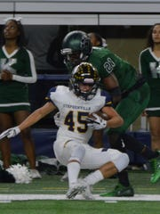 Stephenville's Krece Nowak falls out of bounds after catching a pass while Kennedale's Larry Brooks (21) defends during KHS' 54-28 win over Stephenville in a 4A DI state semifinal at Arlington's AT&T Stadium in 2017.