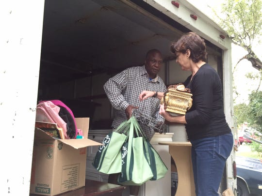 Mover Ordis Collier and Re-New volunteer Cheryl Hays on Thursday unpack items from a moving truck to prepare the new home of a woman moving out of the YWCA's domestic violence shelter.
