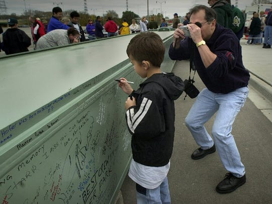 Sean Grabowski, 7, signs an 18 ton box chord while his dad Mike Grabowski takes his picture in this photo from October, 2000. The beam was hoisted above Miller Park and used to keep the roof rigid. Residents from the five counties contributing tax dollars toward building Miller Park were invited to sign.
