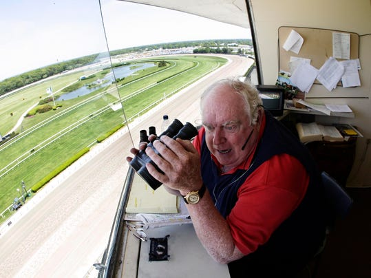 FILE - In this May 26, 2008, file photo,  Belmont Park track announcer Tom Durkin looks down at the homestretch while calling the first race of the day at Belmont Park in Elmont, N.Y. Durkin is calling it quits after 43 years of calling major horse races. He'll bring horses down the stretch one last time on Sunday, Aug. 31, 2014, at Saratoga, ending a career in which he announced Triple Crown and Breeders' Cup winners. (AP Photo/Julie Jacobson, File)