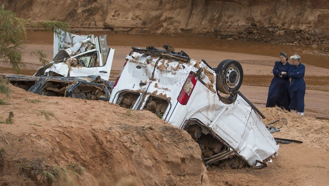 Women look at two vehicles that came to rest in a wash in Hildale, Utah, Sept. 15, 2015. Flash floods washed away two vehicles and a parked car over a ravine, killing several people on Monday Sept. 14, 2015.