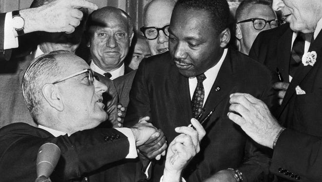 WASHINGTON, :  US President Lyndon Johnson (l) shakes hands with the US clergyman and civil rights leader Martin Luther KIng (c) 03 July 1964 in   Washington DC, after handing him a pen during the ceremonies for the signing of the civil rights bill at the White House.   Martin Luther King was assassinated on 04 April 1968 in Memphis, Tennessee. James Earl Ray confessed to shooting King and was sentenced to 99 years in prison. King's killing sent shock waves through American society at the time, and is still regarded as a landmark event in recent US history.