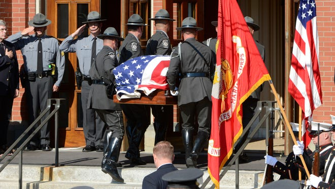Pennsylvania state troopers salute as the casket of Cpl. Bryon Dickson is brought into St. Peter's Cathedral on Sept. 18 in Scranton.
