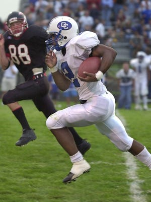 Muskego's Ryan Fitzgerald (left) chases Oak Creek's Brian Calhoun in August 2001. Calhoun still holds the all-time rushing yardage and touchdown records at Oak Creek.