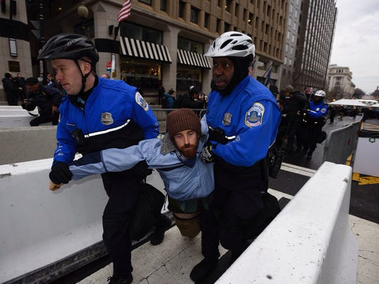 Police removing a protester who was blocking a security checkpoint Friday on 14 St. NW in Washington, D.C.