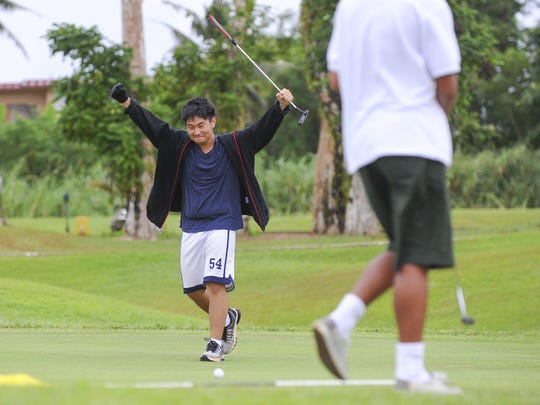 Majesty Christian Academy Crusaders' Min Chang raises his arms in celebration after sinking a long putt during the Independent Interscholastic Athletic Association of Guam Golf League match against the John F. Kennedy High School Islanders at the Guam International Country Club in Dededo on Thursday, Oct. 15.