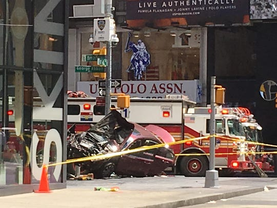 A smashed car sits on the corner of Broadway and 45th Street in New York's Times Square after driving through a crowd of pedestrians May 18, 2017.