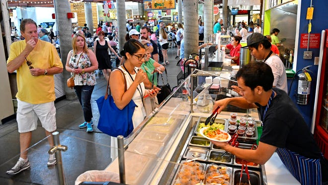 Customers watch their food being prepared May 26, 2017, at Bowl 'n' Roll at the Market House at the Nashville Farmers' Market.