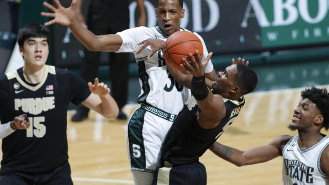 Purdue's Brandon Newman, right, goes to the basket but is blocked by Michigan State's Marcus Bingham Jr. as Purdue's Zach Edey, left, and Michigan State's Aaron Henry watch during the first half of an NCAA college basketball game Friday, Jan. 8, 2021, in East Lansing, Mich.