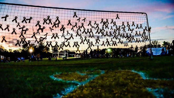 Yellow ribbons dedicated to cancer victims are hung on a net during the Mason/Okemos boys soccer game which was also a fundraiser for Compete for a Cause Saturday September 26, 2015 in Okemos.