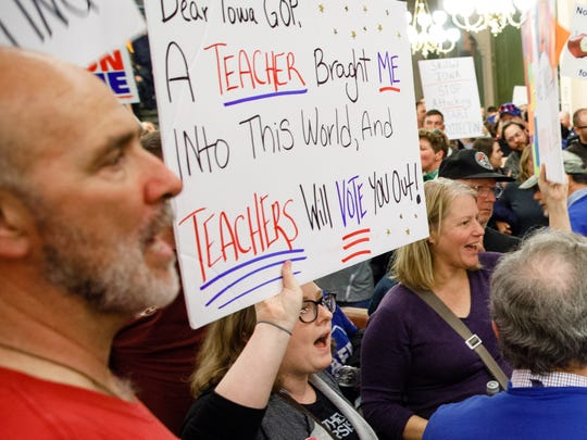 Pro-union demonstrators hold signs and chant as supporters of Americans for Prosperity-Iowa leave Monday, Feb. 13, 2017, after Iowa legislators held a public hearing to discuss proposed changes to Iowa's collective bargaining laws at the Iowa State Capitol in Des Moines.
