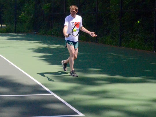 Mark Fury, of Rochester returns a serve at the Pride Games tennis tournament at Cobbs Hill Sunday, July 10, 2016.