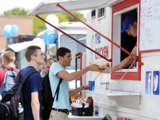 Joey Devor, owner and operator of The Chicken Truck, hands Penn State York freshman Vincent Gurreri his order during a food truck fair on Wednesday, Aug. 27, 2014, on campus.