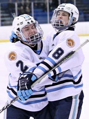 After scoring the tie-breaking goal late in the third period Wednesday, Livonia Stevenson's Austin Adamic (8) is congratulated by Connor Jakacki (2).