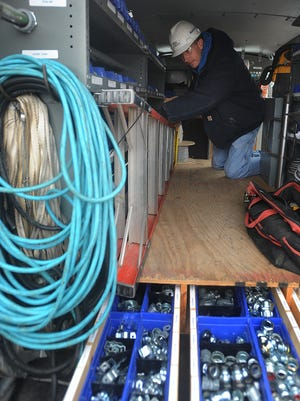 Muth Electric, Inc.'s Service Technician Ben Veltkamp looks for parts in the back of his van.