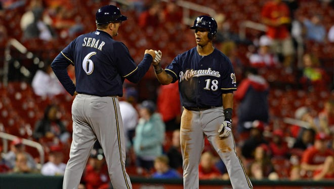 Milwaukee Brewers left fielder Khris Davis, right, is congratulated by third base coach Ed Sedar after hitting a one run triple off of St. Louis Cardinals relief pitcher Seth Maness, not pictured, during the twelfth inning at Busch Stadium.