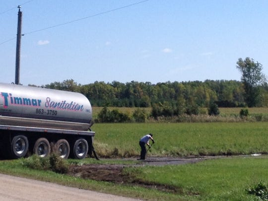 A worker directs manure into the path of a suction device as the cleanup of a 640,000-gallon spill continues Wednesday in the Door County town of Brussels.