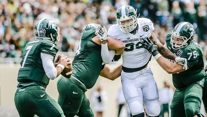 Demetrius Cooper ,center, of the Whte team fights through a double team to pressure Green team quarterback Tyler O'Connor ,left, during the MSU Spring Football game Saturday April 25, 2015 at Spartan Stadium in East Lansing. KEVIN W. FOWLER PHOTO