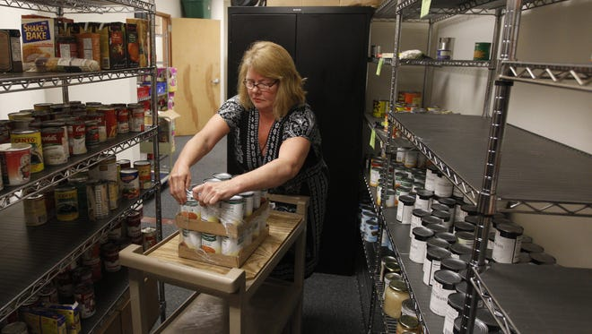 A case manager adds canned goods to the shelves of the Catholic Family Center's food pantry. The center serves all of Monroe County.
