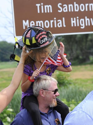 Tim Sanborn's firefighting helmet is a little big for grandaughter Sydney Freeland, 6, held by dad Tim Freeland, after ceremonies for the Tim Sanborn Memorial Highway dedication on US 127 north of St. Johns Monday. Sanborn, of Clinton Area Fire and Rescue, died in 2007 of a heart attack while operating pumps at the scene of a fire.