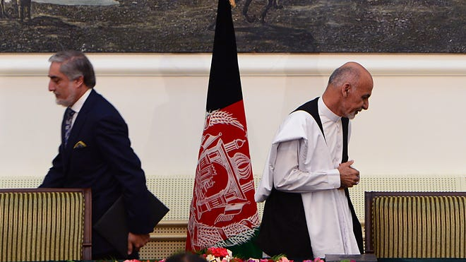 Afghan presidential candidate Ashraf Ghani Ahmadzai, right, leaves after signing a power-sharing agreement at the Presidential Palace in Kabul.