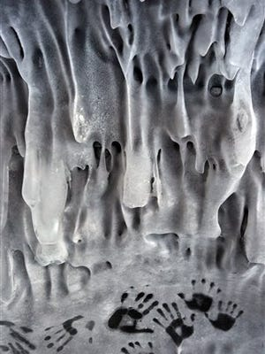 This March 11, 2014, photo shows hand prints left by visitors to one of the ice formations in the ice caves at the Apostle Islands National Lakeshore on the shores of Lake Superior near Bayfield, Wis. Officials said Wednesday, March 14, that the ice caves will soon be closed due to ice melt.