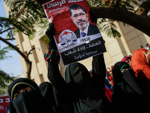 A supporter of Egypt's ousted President Mohammed Morsi holds an old presidential campaign poster of him with Arabic that reads,