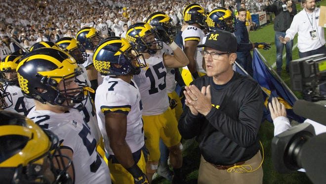 Michigan head coach Jim Harbaugh talks with his team before their game against Penn State on Saturday.