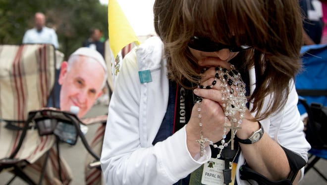 Laura Bugay, of Green Township, N.J., holds her children's rosaries as she prays during the a Mass celebrated by Pope Francis on Benjamin Franklin Parkway in Philadelphia, Sunday, Sept. 27, 2015. In the background at left is a cardboard cutout of Pope Francis. (AP Photo/Carolyn Kaster)
