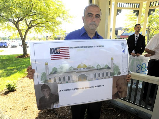 Khalil Abbass, of Troy holds an artist rendering of the proposed Sterling Heights Mosque.