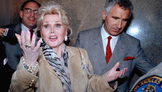 In a May 1, 1990 file photo, Zsa Zsa Gabor gestures as she while answering questions as she leaves the Beverly Hills courtroom where judge Charles Rubin ruled that she violated her probation. Gabor was ordered to complete her community service at a Venice homeless shelter, with an additional 60 hours. At right is her husband Frederick von Anhalt. Gabor died Sunday, Dec. 18, 2016, of a heart attack at her Bel-Air home, her husband, Prince Frederic von Anhalt, said. She was 99.