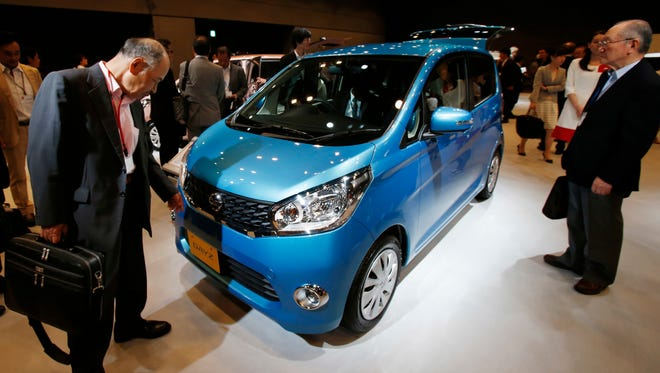 """In this June 6, 2013, file photo, visitors check Nissan's compact car """"DAYZ"""" after a press conference in Tokyo."""